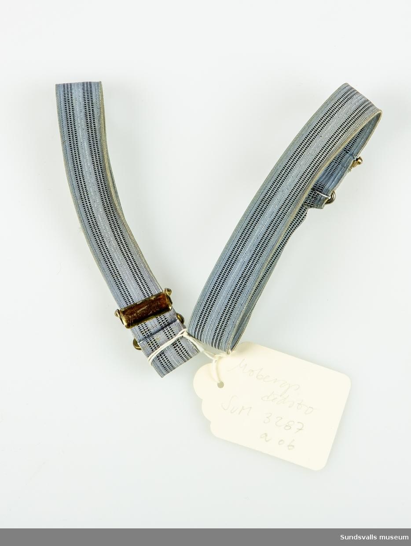 SuM 3287:a-b strumphållare i grå- och svartrandig resår. Spännen av gul metall.