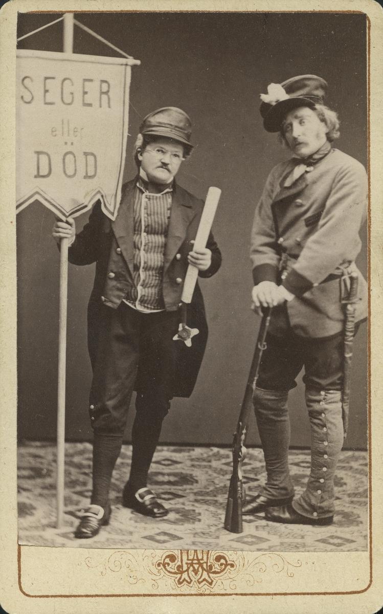 """Conny Hedman, Nordström. Två män iförda teaterklädsel. En håller i ett standar med fana som lyder """"Seger eller död""""."""
