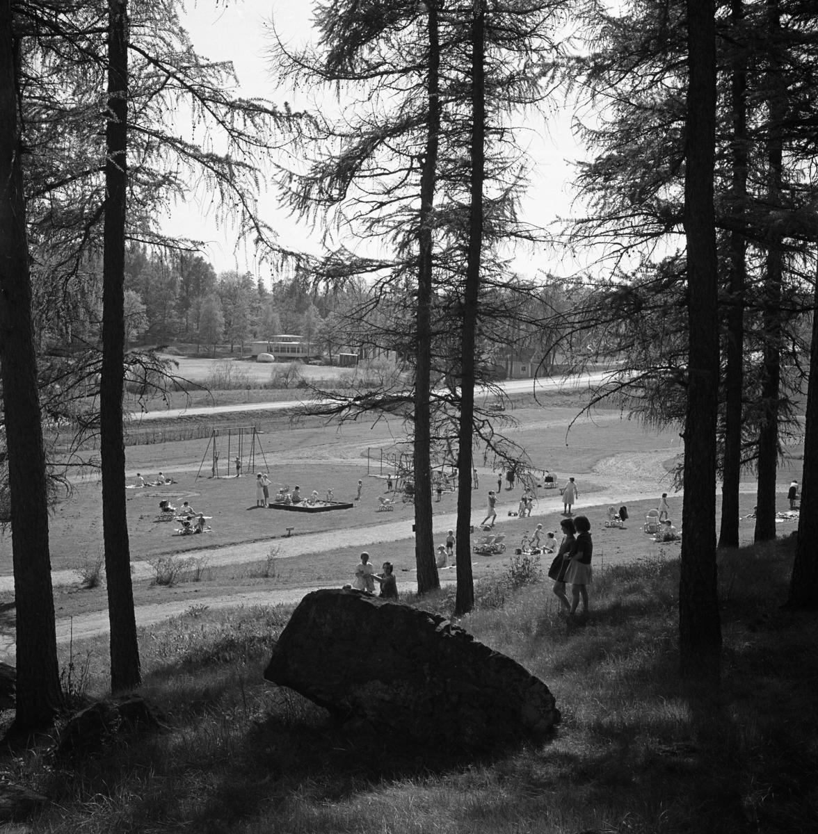Utsikt från Törnberget. En lekplats med gungor och sandlåda håller många barn sysselsatta. I bakgrunden ses restaurang Vinbäcken och Brunnshuset.