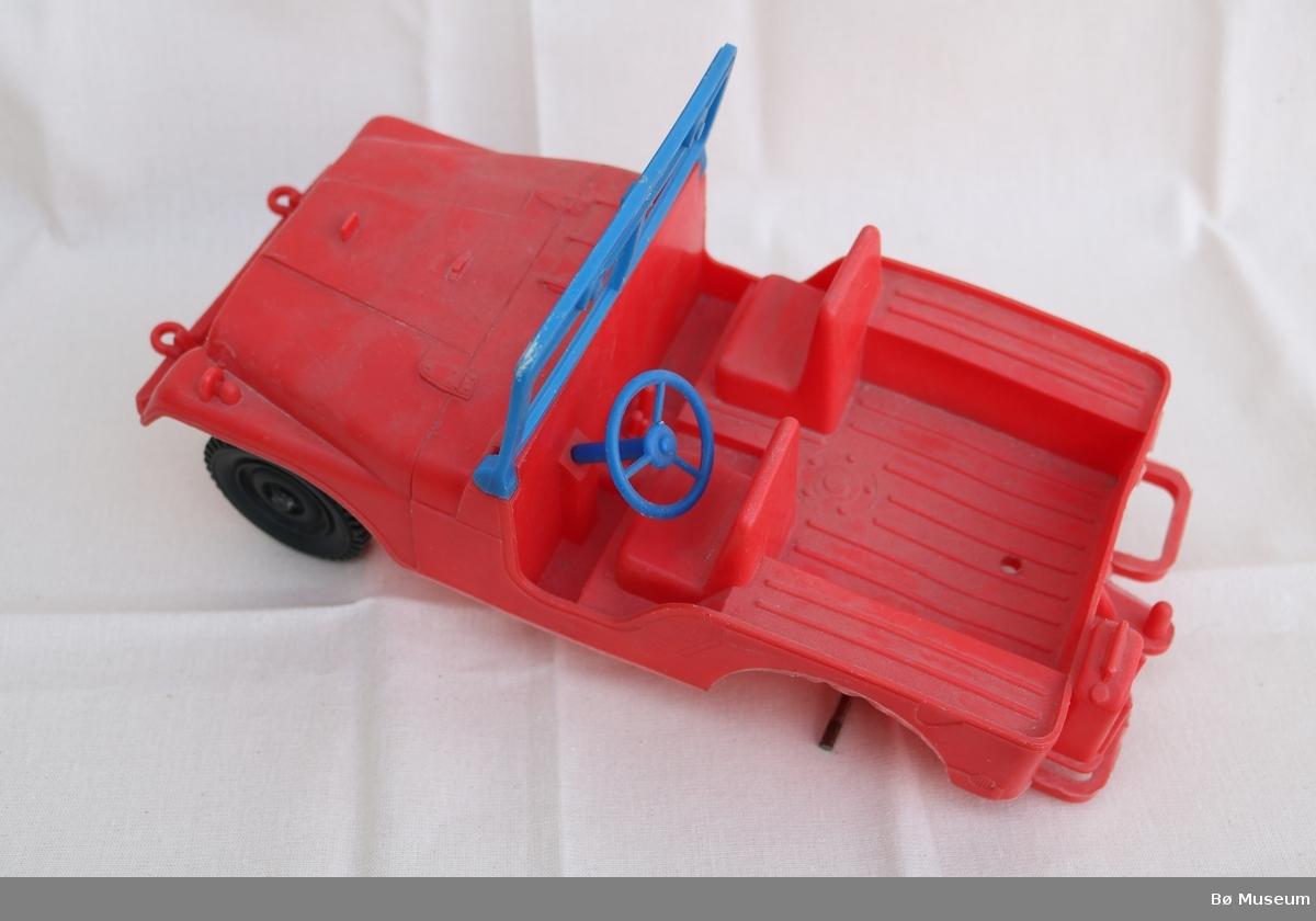 Leikebil i plast. Frontruta kan leggast ned. Hjul er festa med stålstenger. Venstre bakhjul manglar.