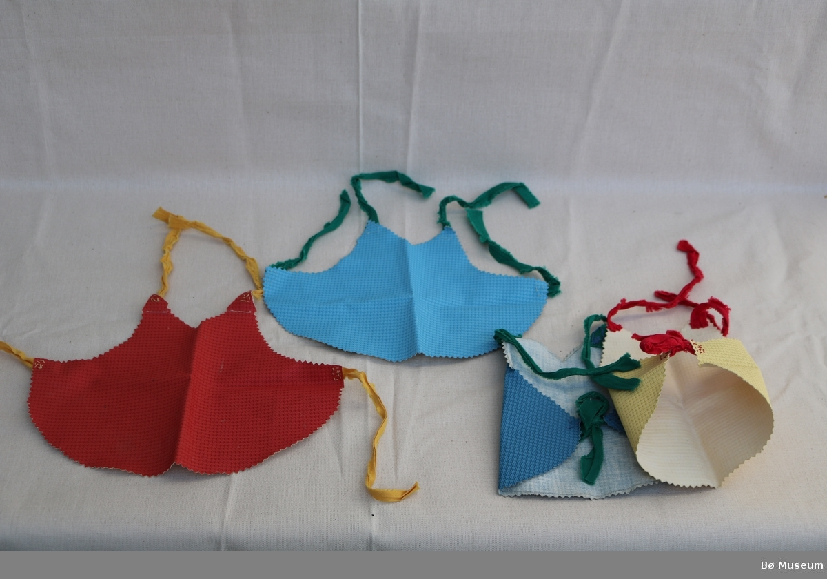 Veske (a) med håndtak og glidelås. Det er bilete og tekst på, og ein avstivar inni veska. Festa sammen med naglar, og det manglar ei på venstre kortside. Inni er det ei lenke (b), og dokkeklede og forskjellige tekstilbitar. Fire forklede (c) laga av eit stykke tøy som er klypt ut med sikksakksaks, med tøyremser påsydd for hånd. Fem bomullsband (d). Strikka gul lue med dusk (e). Kjole med fald (f), utan ermer, laust belte sydd i samme samme stoff som kjolen. Strikka topp utan erme (g). Underbukse med strikk i livet og beina (h). Kyse med påsydde tøyremser (i). Strikka raud lue med dusk (j). To tøflar (k). Grønt pannebånd (l). Lita underbukse (m). Rosa pannebånd (n). Skjerf (o). Dobbelttvinna tråd (p). To små kleshengere i plast (q), den eine med støpt rosemotiv. Ein strikka sokk eller vott, med ribbekant (r). Ei dokkebluse (s) og -bukse (t) i same stoff, med elastiske ribbestykke rundt halsopning, armar og bein. Buksa har strikk i livet. Blusa kan lukkast med to trykknappar.