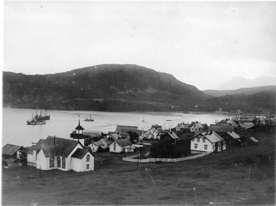 Vy över Skjaervö. Kyrkan närmast i bild till vänster. Flera båtar vid hamnen.