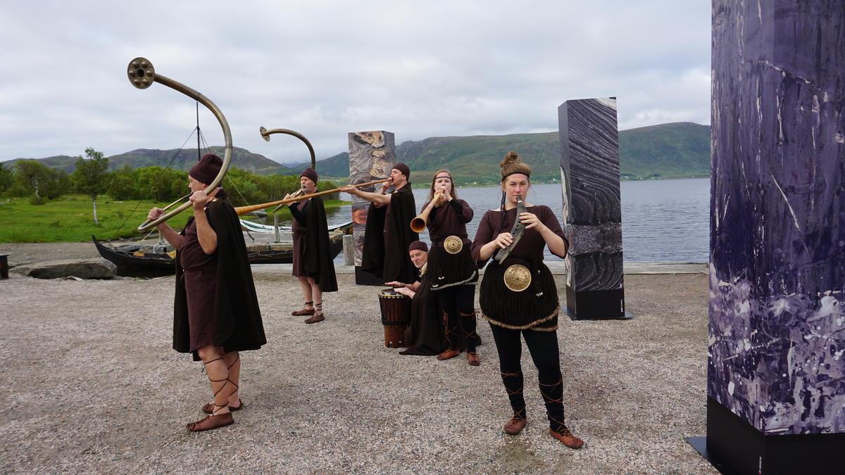 Bronsealderkledd band som spiller på bronselurer utendørs.