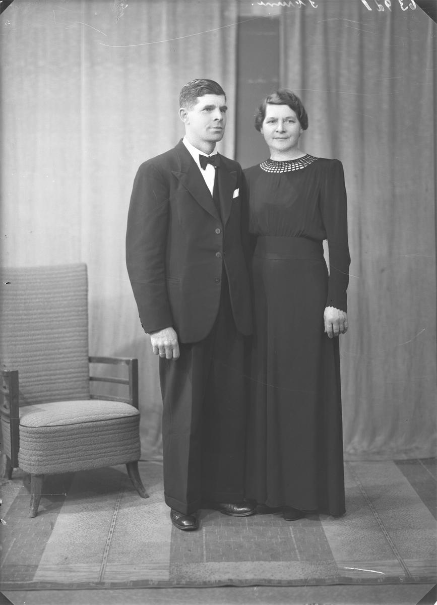 Gruppebilde. Familiegruppe på to. Ung mann i mørk dress, mørk vest, hvit skjorte og mørkt slips med stiper, ung kvinne i lang mørk kjole med knapper. Søsken. Festkledd. Bestilt av Sigvald Gåsland. Skåredalen.