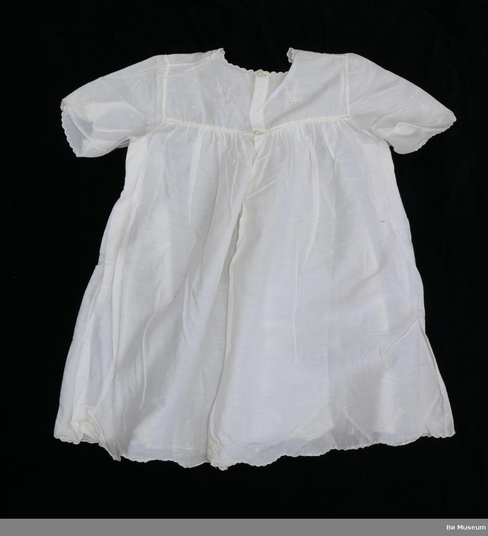 Kvit nattkjole for baby. Brodert med plantemønster av kvit tråd på bryst og på rygg. To knappar i nakken. Kvit, bølgete søm rundt hals og i botn.