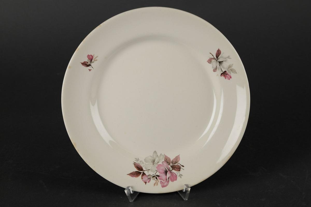 Hvit tallerken dekorert med tre blomster langs kanten.