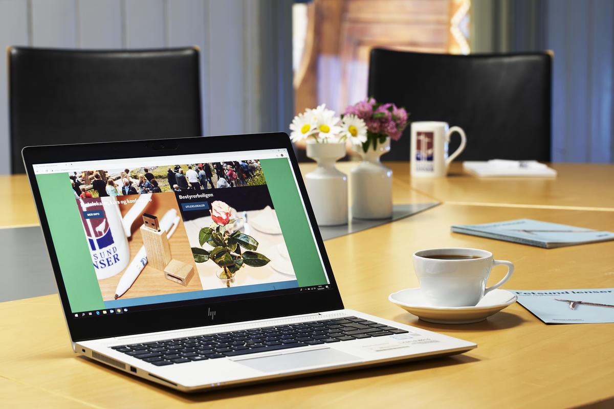 Bærbar pc i forgrunnen med kaffekopp og folder på høyre side på et konferansebord. Blomster og kaffekopper i bakgrunnen (Foto/Photo)