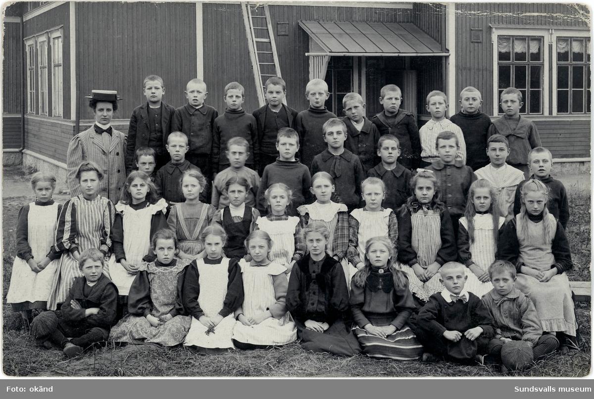 """Klassbild med barn från Skönsmons skola. Skolbyggnaden i bakgrunden. Brevkortet är poststämplat den 9:e november 1908. Texten på baksidan innehåller dessa rader: """"...Här ser du min klass minus 11 st, inalles är de 49. En liten nätt skara, eller hur?"""" Flickan/pojken har undertecknat med """"Lasse-Maja"""" och skickat kortet till fröken Elin Wallin, Göteborg."""