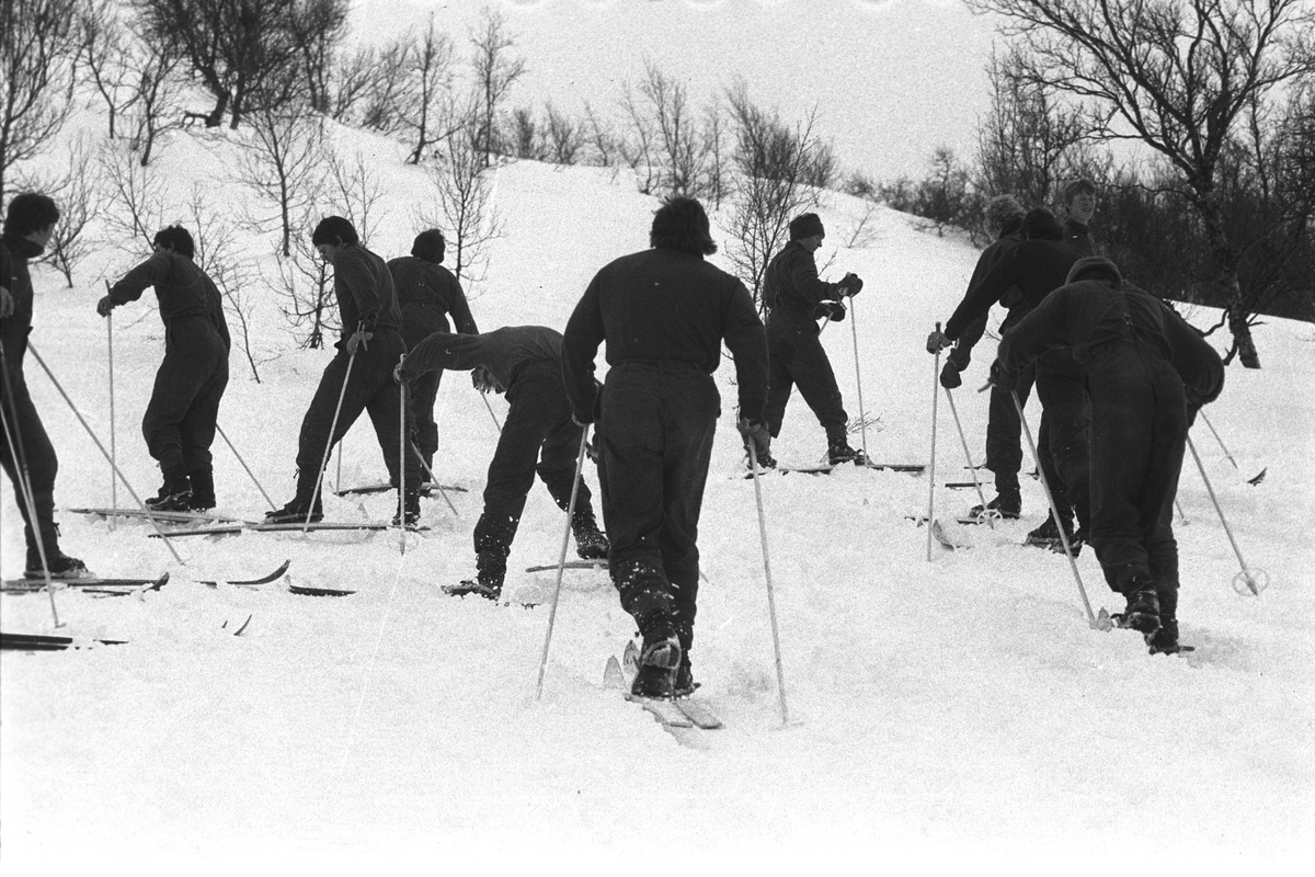 Befalsskoleelever på ski går opp bakke.
