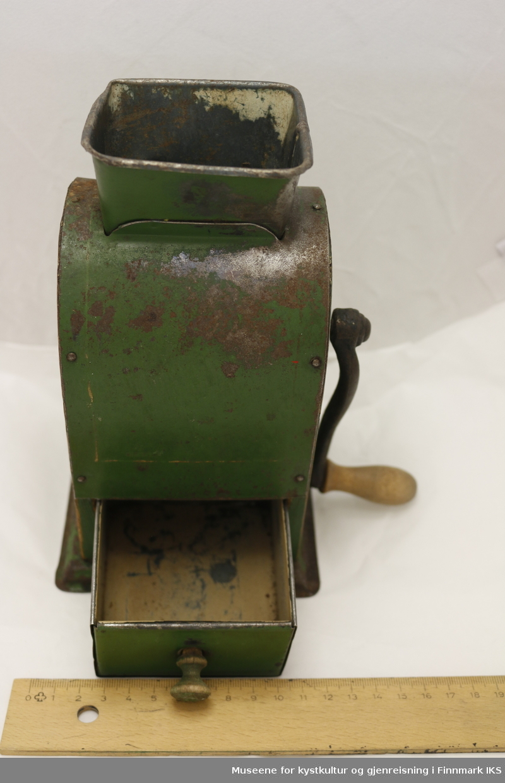 Grønn kaffekvern med sveiv. Kaffekvernen har skuff under kvernen, innmatingstrakt av metall i toppen, og sveiv til kvernen på høyre side. Toppen av kaffekvernen er buet, og den står på en metallfot.