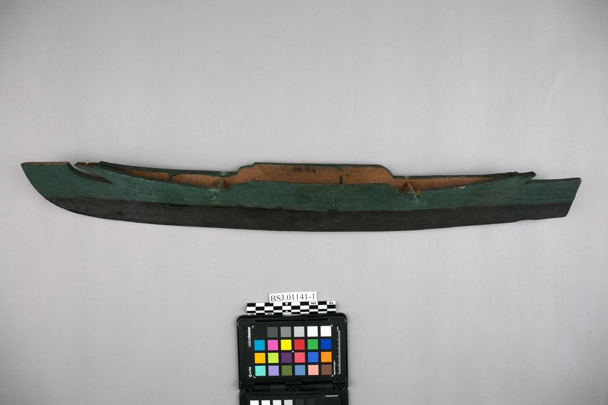 Kano. Modell av australsk utriggerkano med utrigger, padleåre, spyd, taukveil og andre løse deler. Kano er lang og smal og er litt høyere i midten.