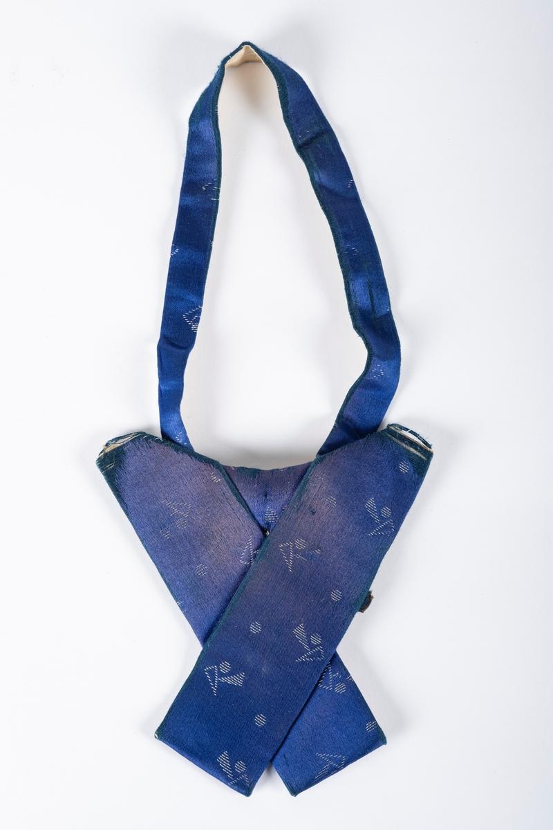 Sløyfe i blått tekstil med hvite geometriske motiver. Sløyfens ender ligger i kryss over hverandre. Under tekstilet er det papp som stiver av sløyfen, og en metallspenne der båndet rundt halsen kan festes.