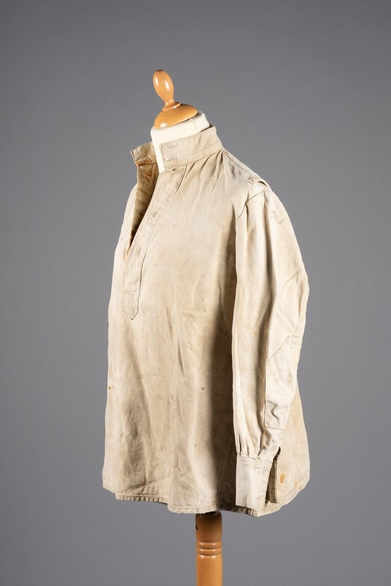 Skjorte med lange ermer og høy krage. Det er knepping i front. Alle knappene mangler, også mansjettknappene. Ermene har albueforsterkning. Det er en smygstol på hver skulder.