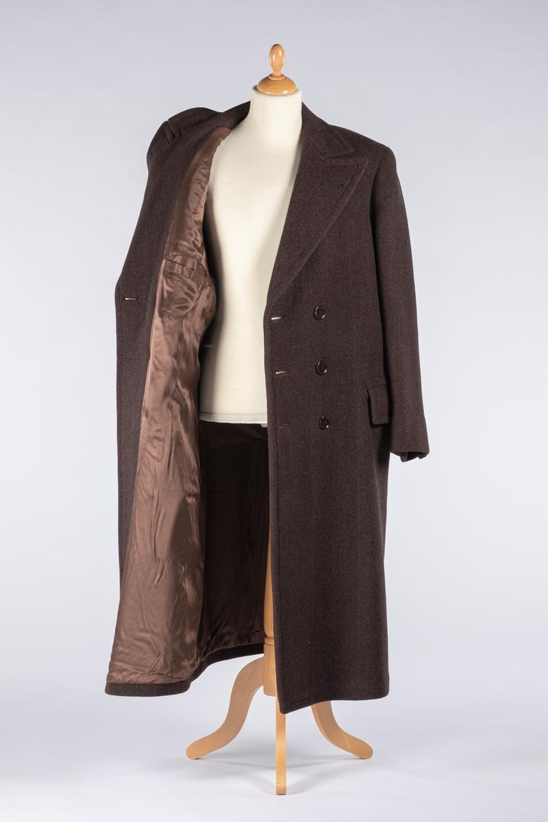 Fiskebensmønstret frakk med slag. Frakken er foret med silke. Den er dobbeltspent. Den har to forlommer med klaff og en innerlomme. Forlommene er foret med bomull. Det er splitt bak.