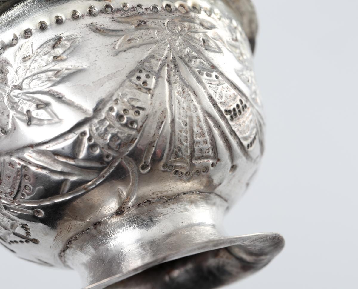 Två supkoppar av tunnt, drivet silver. Försedda med ciselerad eller pressad dekor på sidorna. Kopparna är försedda med en pålödd fot samt räfflade öron.  I botten (på utsidan) är stämplar islagna.