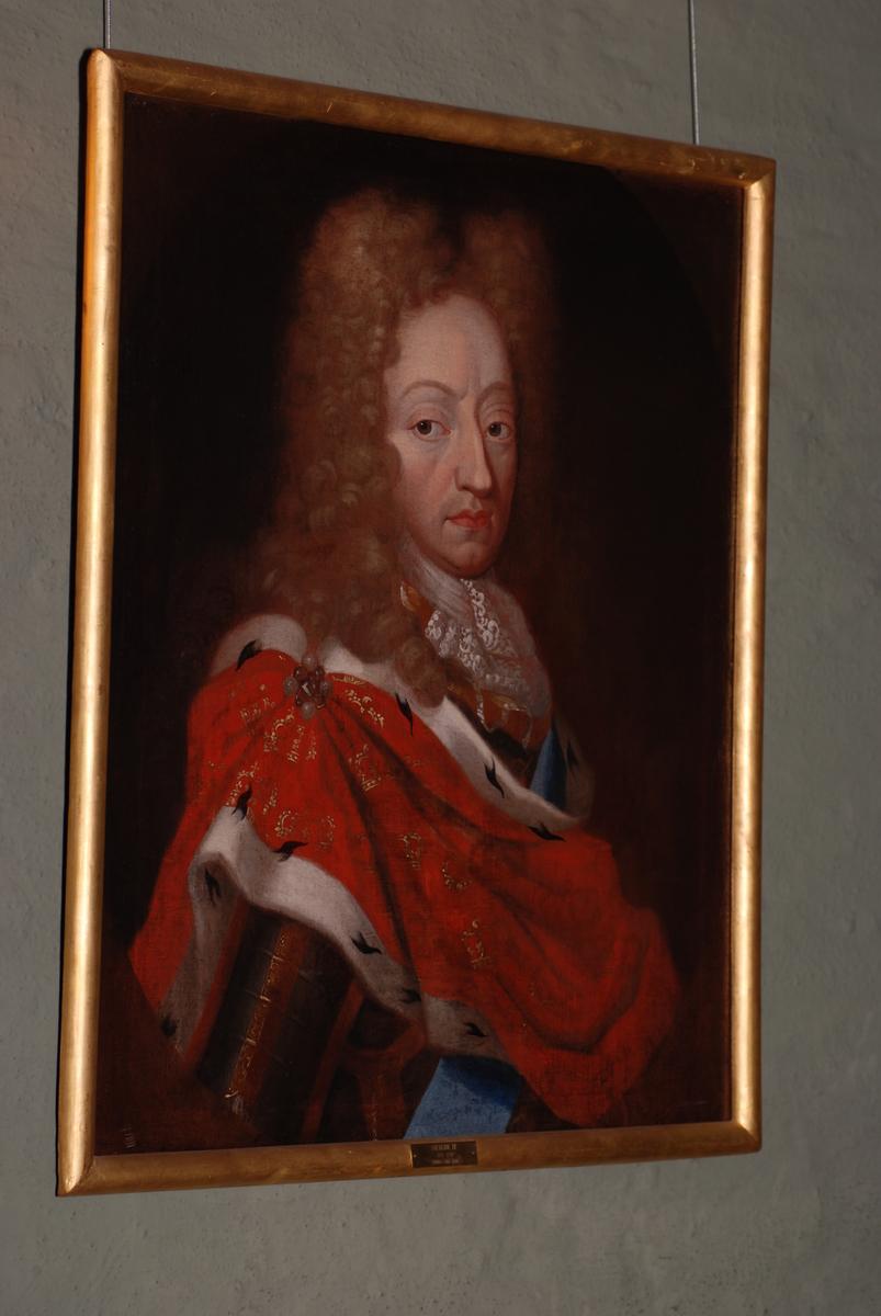 Olje på lerret, portrett av Fredrik IV 1671-1730. Halvfigur. Kroppen i halv profil mot høyre, hodet i kvart profil mot høyre. På skrå over brystet en rød kape med gullkroner og hermelinskanter. Forgylt ramme.