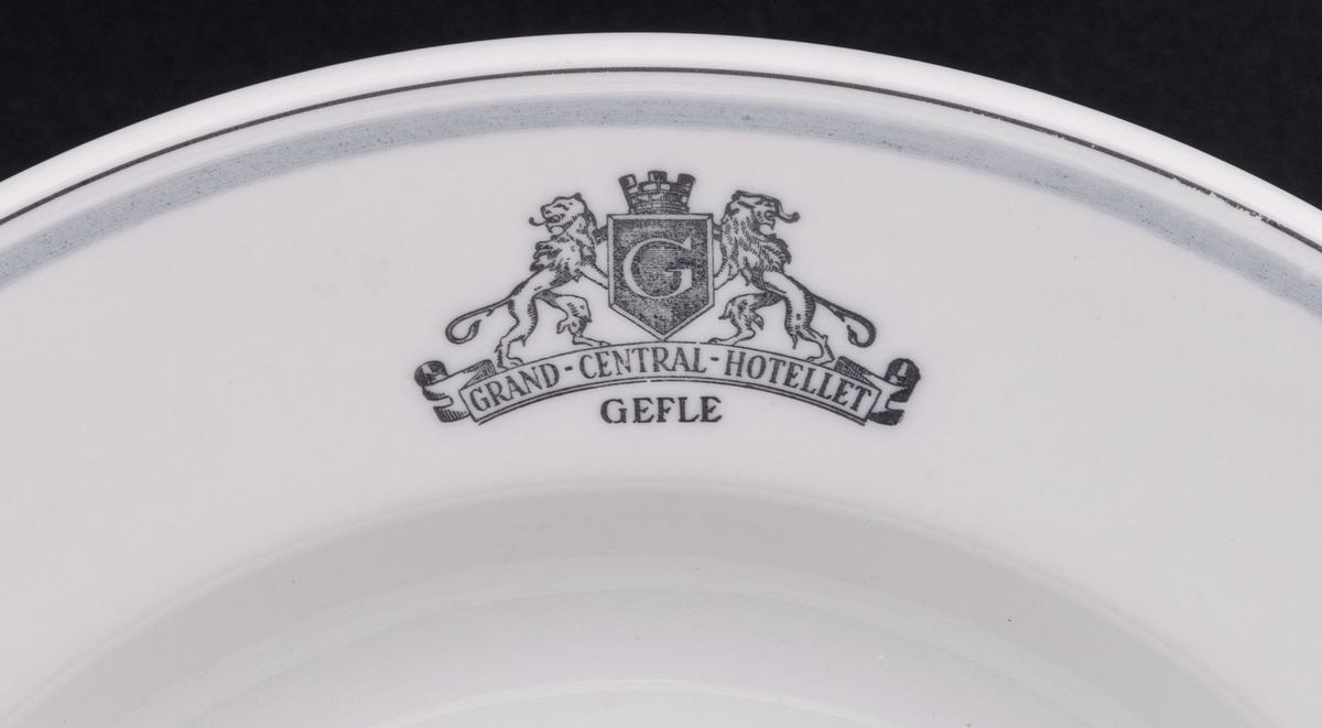 Tallrik, djup. Vit glasyr med ljusgrå och mörkgrå dekor. På brättet emblemet Grand Central Hotellet Gefle, samt två lejon hållande Gävle vapen. Ytterast på brättet två tunna grå ränder.