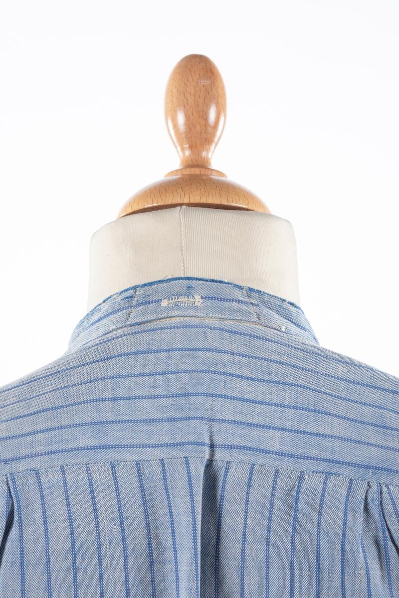 Skjorte i blåstripete bomullslerret. Bolen er sydd med et par legg til skulderstykket som er forsterket på innsiden med hvit bomullslerret. Isydde ermer med 5 cm.bred manjett. Forstykket har avrundede hjørner. Det er splitt i hver side. Halsåpningen lukkes med 2 knapper. På kragen er det tre knappehull.