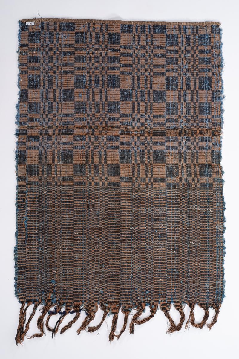 Teppe med brun og svart renning og blå filler innslag (filleryteknikk). Det er dusker på ene kortsida.