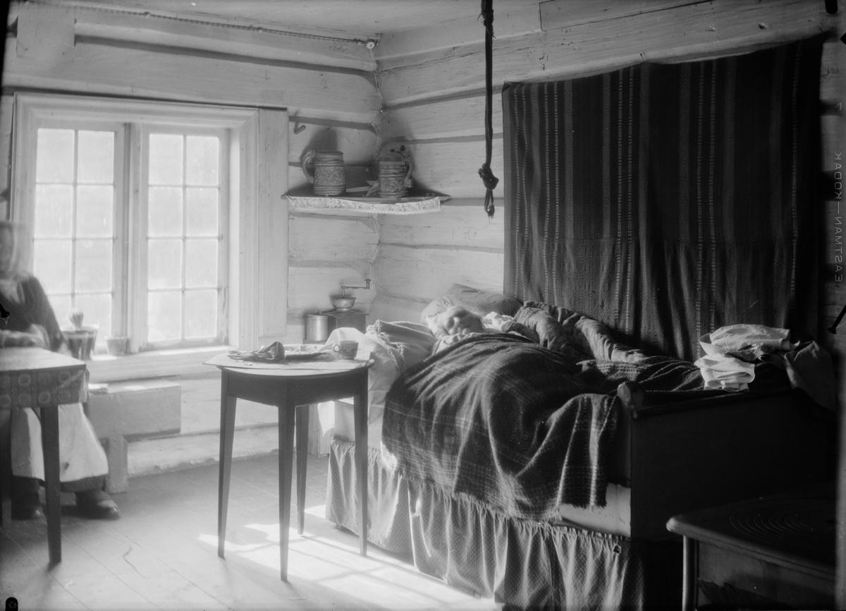 Gammel kvinne ligger til sengs med åkle over dyna og sengestropp, også nevnt som Anton, henger ned fra taket. Utskjærte ølkrud på hylle ved vinduet