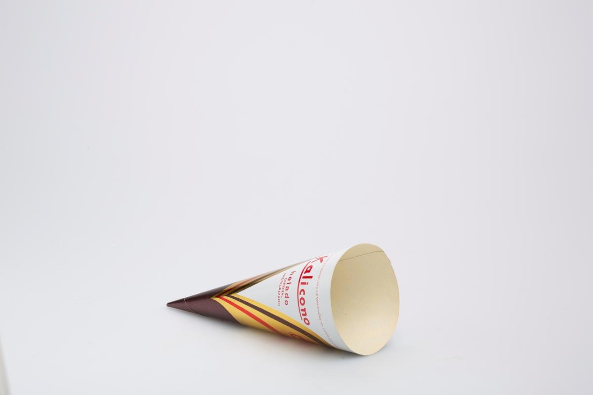 Kjegleformet iskrempapir (kremmerhus) i papir og aluminium. Kremmerhuset er med farger på utsiden, og uten farge (hvit) på innsiden. Kremmerhuset har hvit bakgrunn og buet mønster i gull med brun og rød stripe.