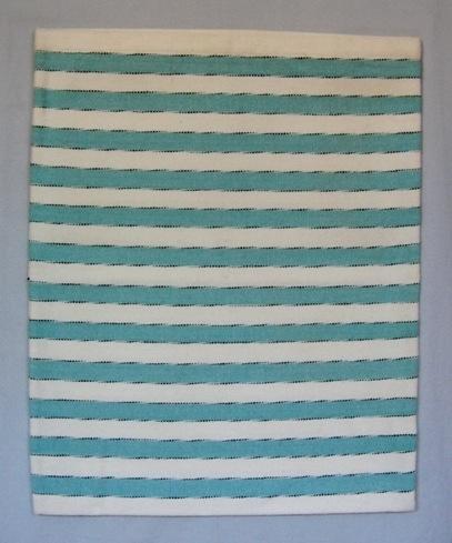 Ett randigt kuddvar sytt som ett örngott med ficka. I varpen blekt bomullsgarn 8/2 och i inslaget dubbelt blekt, svart och grönblått möbeltygsgarn. Den invikta fickan är vävd i tuskaft utan mönster och endast zick-zackad i kanten.  Kuddvaret är märkt med R36:1 på ett vitt bomullsband.  Kuddvar med modellnamn Ika är formgivet av Ann-Mari Nilsson och tillverkat av Länshemslöjden Skaraborg. Det finns med  på sidan 84-85 i vävboken Inredningsvävar av Ann-Mari Nilsson i samarbete med Länshemslöjden Skaraborg från 1987, ICA Bokförlag. Se även inv.nr. 0001-0035,0037-0040.
