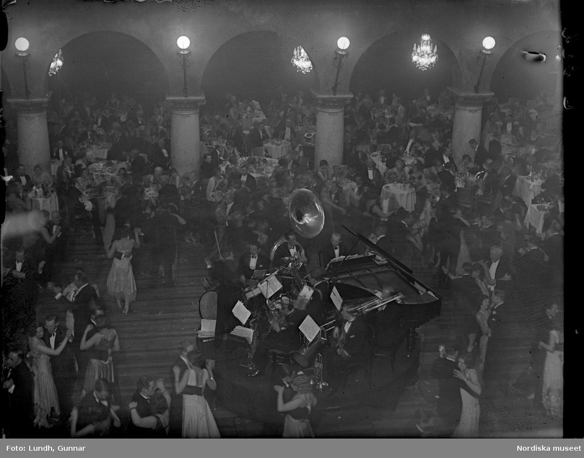 Motiv: (ingen anteckning) ; Interiör troligen av Grands Vinterträdgård med festklädda människor som dansar till en orkester, festklädda kvinnor och män sitter vid ett bord med glas och vinflaskor, två kvinnor eldar vid en gryta som hänger över en öppen eld utomhus, ett barn sitter vid två hundar som är kopplade med en kedja.