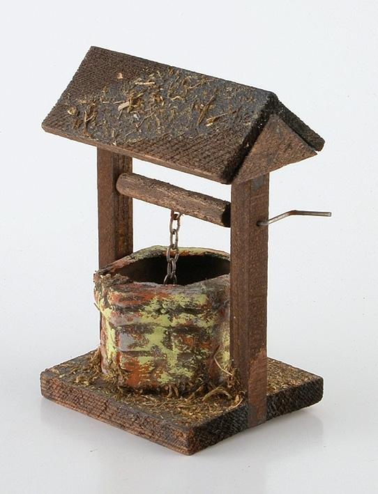 Brunbetsat trä patinerat med mossa. Bottenplatta med 2 st stolpar som bär upp taket. Mellan stolparna en träbeklädd metallvev varpå en kätting med plåtspann är fäst. Spannen sänkes ned i ett brun- och gulmålat brunnshål.