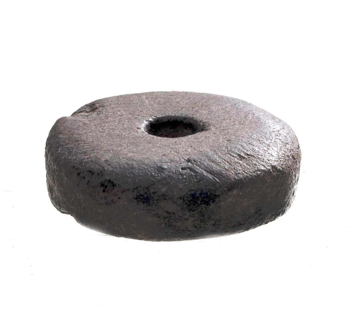 Flatt, sylindrisk spinnehjul av mørk brunlig sandstein, av typen [Rygh fig.434]R. 434.