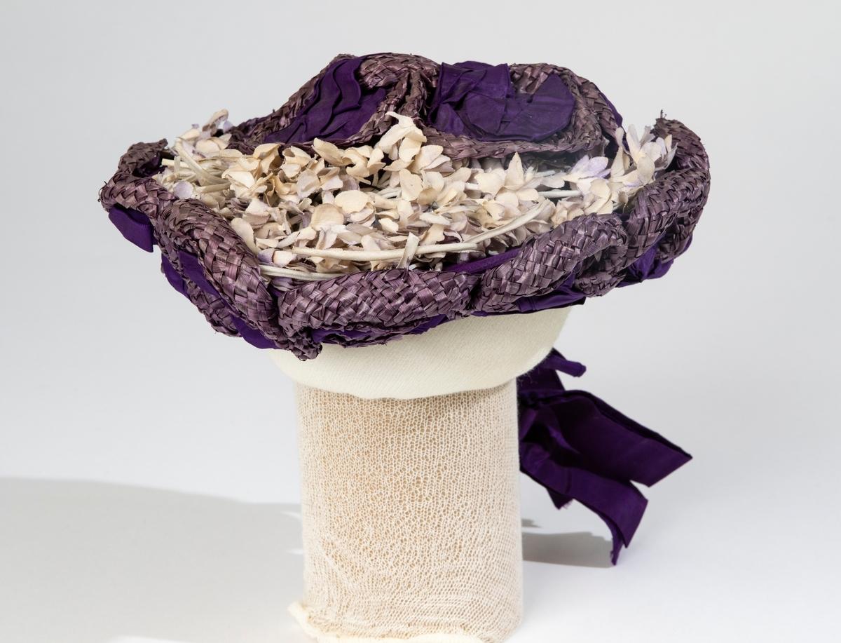 """Stråhatt, kapott, för dam i lila flätat strå med lila sidenband och små, vita tygblommor på kullen. Hatten har uppåtgående brätten formade till kronblad. Baktill på hatten är brättet uppvikt över kullen, där brättet slutar finns lila sidenband knutna till en rosett. Inuti brättets """"kronblad"""" finns lila sidenband, som även klär hattens nederkant mot ansiktet. Hatten är fodrad med svart sidenfoder och i kullen är stämplat med guldfärg: """"Augusta Landberg MODES GÖTEBORG""""."""