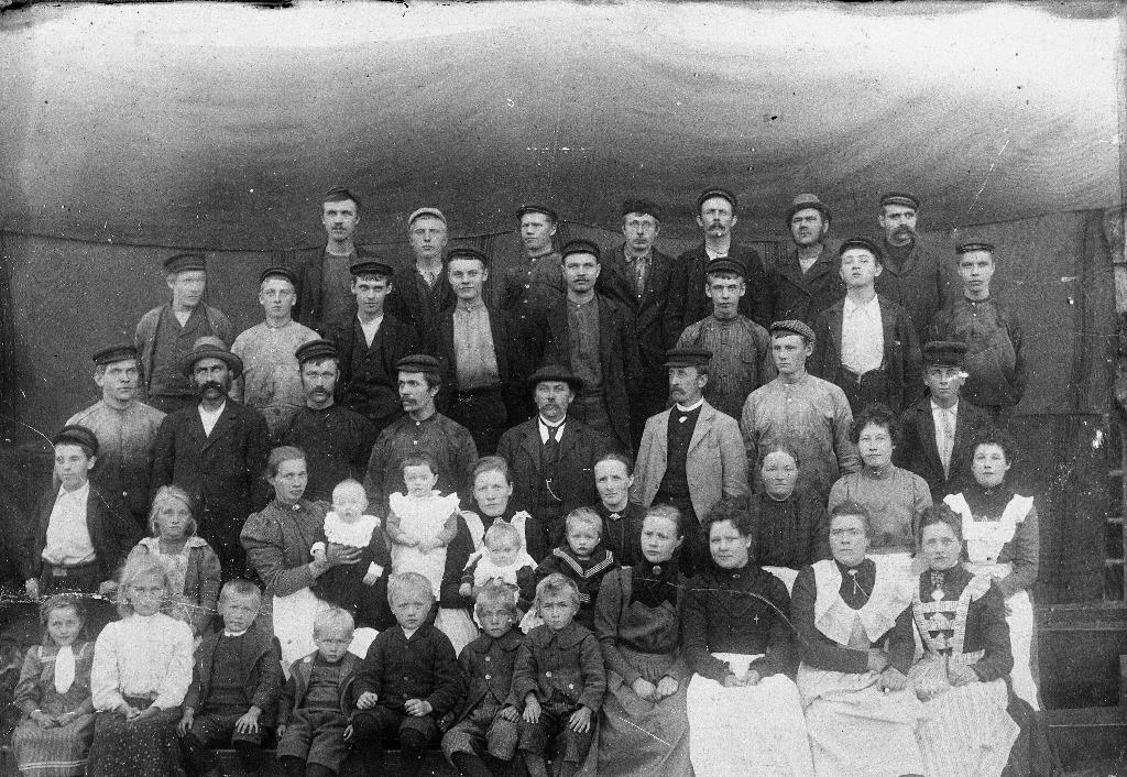 Folk som budde i Kverneland sentrum i 1901. Midt på biletet: O.G. Kverneland (1854 - 1941) med hatt, til venstre framfor han sit kona Anna Malena Ådnesdtr. f. Åsland (1863 - 1946) med Ola (Ole Gabriel (1901 -1964) på fanget. 1. rekkje f. v. : Malena Øyri, Rakel Kverneland (faster til Gunvor Bolme), Andreas Eide, Br. Kverneland i Stavgr., Ådne Kverneland, Olaus Kverneland, Reinert Kverneland og Martin Kverneland, Dorthea? Braut, Elen Eide, Karen Tjemsland, Inga Bolme f. Kverneland. 2. rekkje f. v. : Gutt heilt til venstre, Marta Underhaug med Sigrid Underhaug og Karen Underhaug, Anna Malena Kverneland med Ola (Ole Gabriel) Kverneland, Martha Kverneland (bestemor til Gunvor Bolme), Maria Eide, Dina Eide g. Vagle. 3. Rekkje f. v. nr. 2 er bestefar til Gunvor Bolme, Reinert Retsius Kverneland. 4. rekkje f. h. nr. 3 er Alfred Bolme. 3. rekkje
