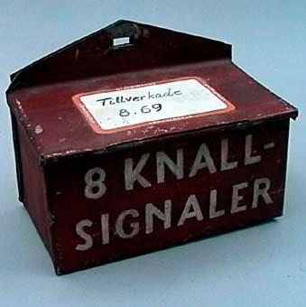 """Knalldoslåda av rödmålad plåt, med texten """"8 knallsignaler"""" målat på framsidan. Lådan har lock och är avsedd för att hängas upp på en vägg eller plan yta.  Utan knalldosor."""