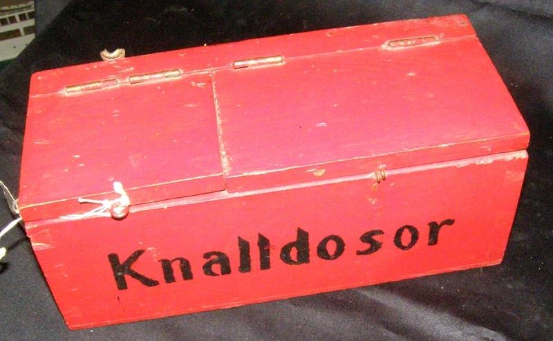 """Rödmålad trälåda för knalldosor, med texten """"Knalldosor"""" målat i svart på framsidan. Locket är tudelat. Lådan är tom."""