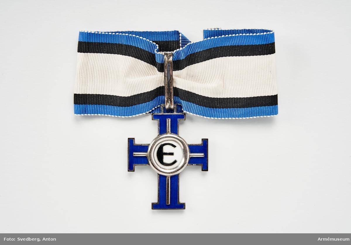 Grupp: M. Andra graden, tredje klassen. Denna dekoration är till form och utstyrsel lika med nr AM.016330, men är till sina proportioner något större, armarnas längd är 8 mm, och korset är av blå emalj, dekorationen bäres om halsen.  Åtsidan: Skiljer sig från no 16330 därigenom att emaljen å upphöjningen är vit samt bär allenast ett E i svart emalj med silverkanter.  Frånsidan: emaljfältet i upphöjningen är vitt. Bandets mittrand är här vit och 17 mm bred, de smala ränderna äro svarta (innerst) och blå.
