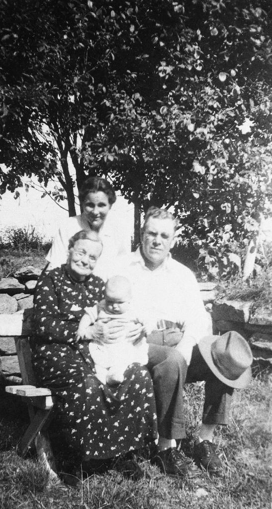 Maja (Ingeborg Maria) Time i hagen med barn på fanget. Sjå også 1990.1TIM.15.002. Ved sida av sit sonen Petter Time som er heime frå Amerika. Bak står dottera Inga.