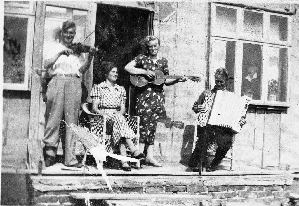 Husorkester på trappa hos Enok Grude på Klepp st. Frå v. med fiolin sit Halvdan Landsnes, Anna Harestad i stolen, Klara Grude g. Bergene med gitar og Erling Grude med trekkspel,