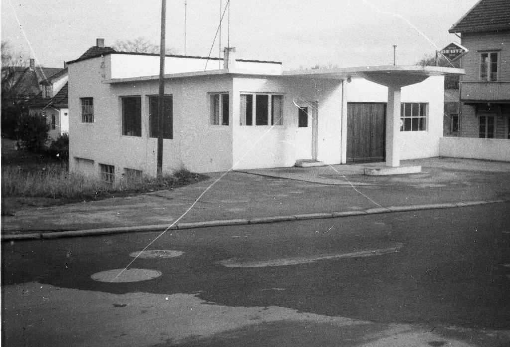 Den første bygningen til Erlands Maskinfabrikk i Storgata på Bryne. Den vart bygd som bensinstasjon i 1939. Vart så teken i bruk som maskinfabrikk i 1941 og riven i 1968. Nå (1990) står bygget til SR-bank der.
