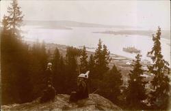 Vykort med motiv av tre kvinnor och vyn över Sundsvallsfjärd