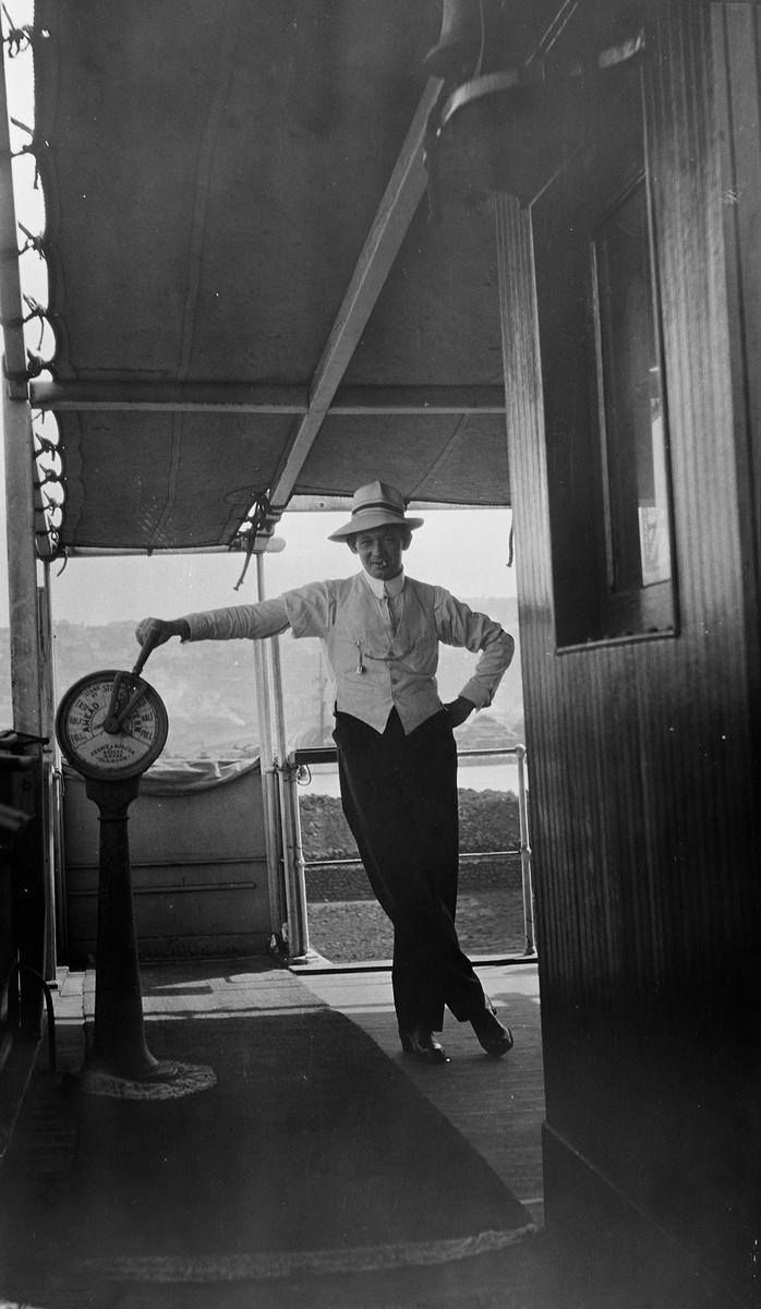 Ung mann med sommerhatt, lys vest og klokke i kjede. Holder på maskintelegrafen utenfor styrhuset ombord på D/S STORFOND.