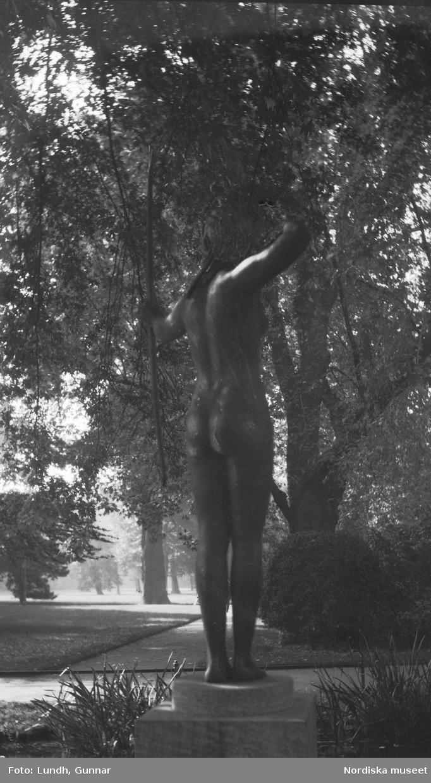 """Motiv: Utlandet, Berlin 114 - 146 ; En skulptur i en park, en mast i fackverkskonstruktion, människor badar i ett utomhusbad och människor sitter på en utomhusservering - en skylt """"Gesamt Bau Ausführung Gottlieb Tesch .......""""."""