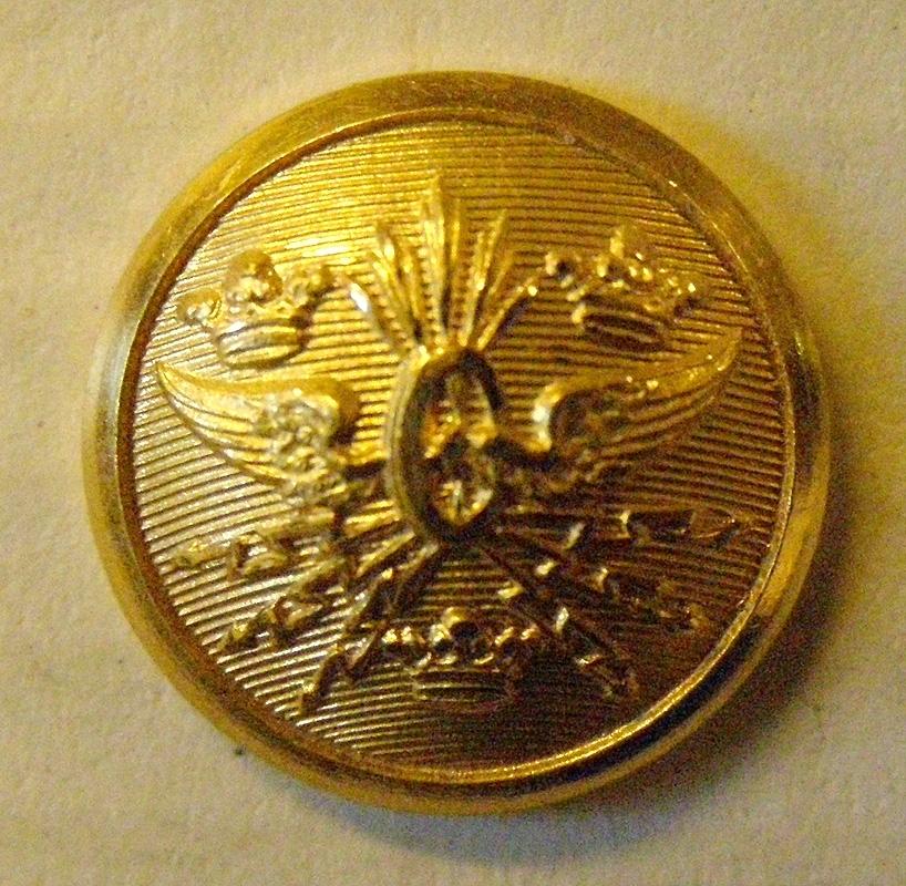 Guldfärgad bottnad knapp med motiv krönt bevingat hjul med blixtar, med vikben som fastsättning på baksidan.