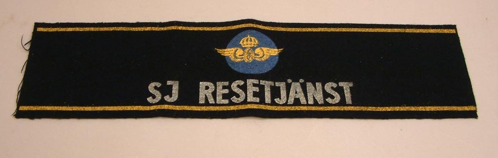 """Armbindel av blåsvart filt för SJ Resetjänst. Blå cirkel med krönt gyllene vinghjul. Texten """"SJ Resetjänst"""" i vitt. 2 gula kantränder."""