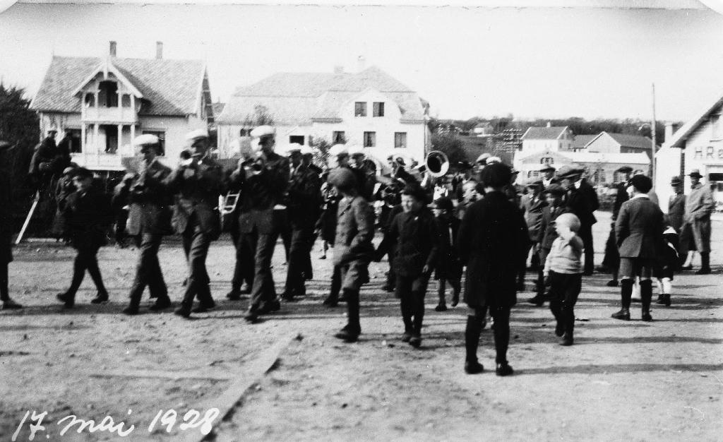 """Bryne Musikkorps spelar på Bryne torg 17. mai 1928. Husa frå v. Blikkenslagar Haarr, """"Festiviteten"""", våningshus og løa på garden til Abram Bryne (seinare Eilef Bryne) med Time Trevare framføre."""