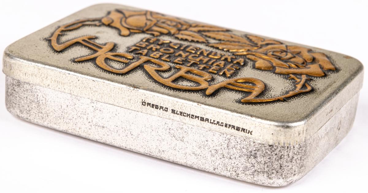 """Tablettask i plåt, silverfärgad botten med rosdekor och text i guld: """"HYGIENISKA BRONCHIALTABLETTEN HERBA""""."""