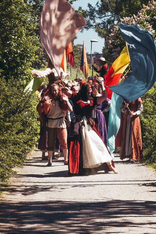 Opptog med glade mennesker kledd i middelalderklær. Alle vifter med store, fargerike flagg.