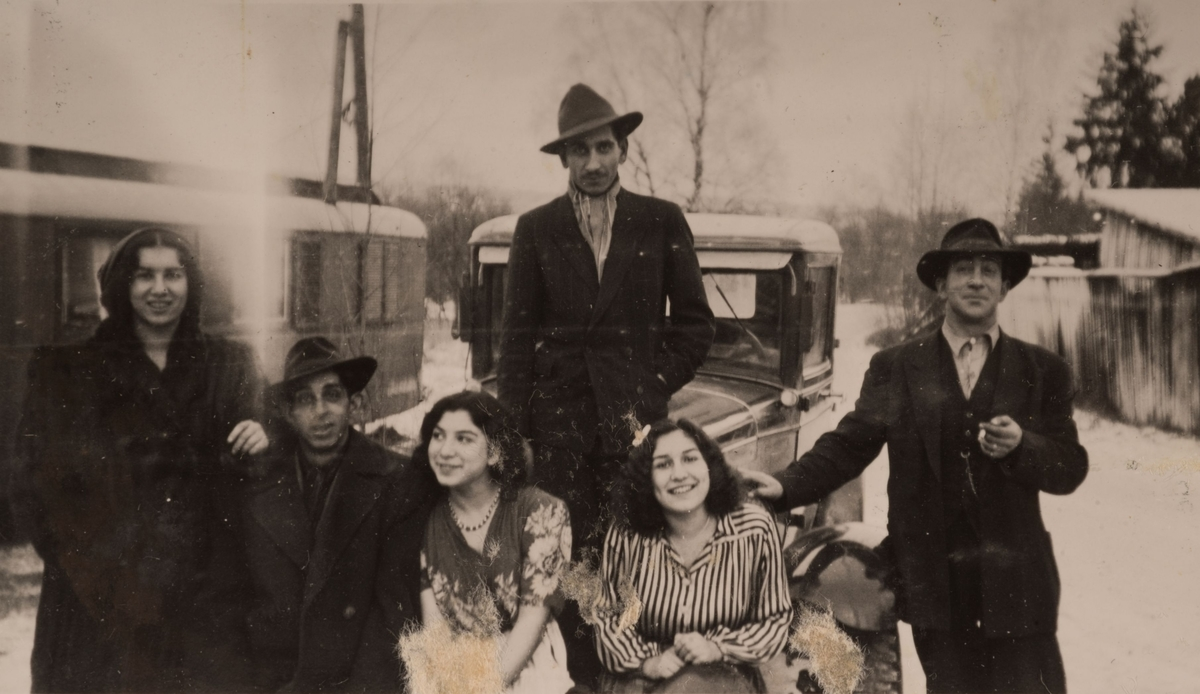En grupp romska män och kvinnor är uppställda framför en bil. I bakgrunden syns en bostadsvagn.  Det känt att en romsk familj bodde i utkanten av Storvik under januari månad 1947. Lägret fanns antagligen i närheten av idrottsanläggningen Parkhallen som ligger i norra delen av Storvik.