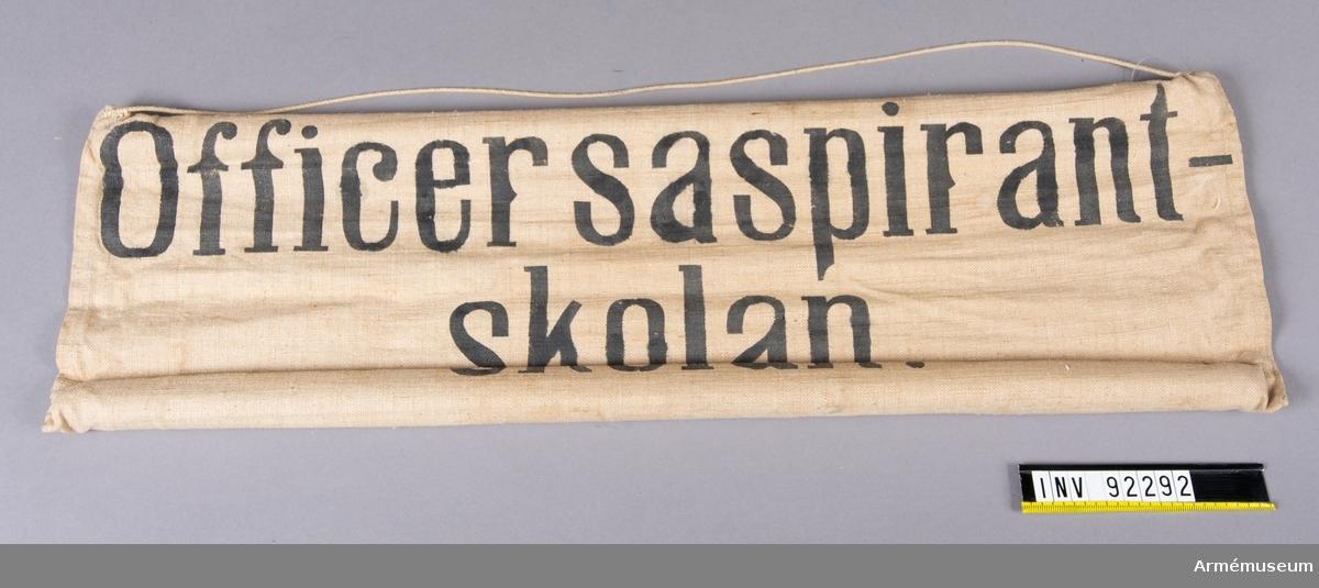 Skylt av tyg med träpinnar i sydda kanaler på långsidorna. Upphängningssnöre. Svart text: Officersaspirantskolan