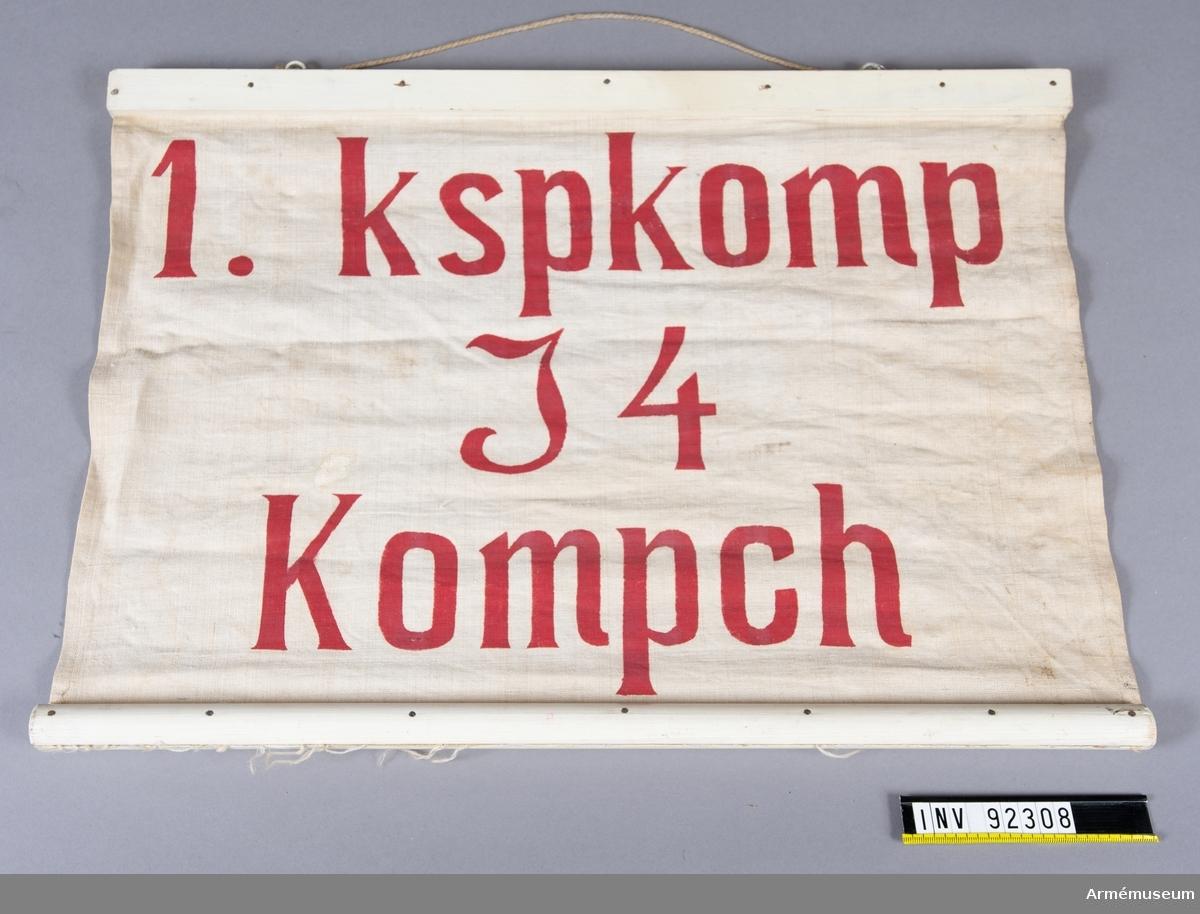 """Skylt av tyg fäst i träpinnar på långsidorna. Röd text: """"1. kspkomp I4 Kompch"""""""
