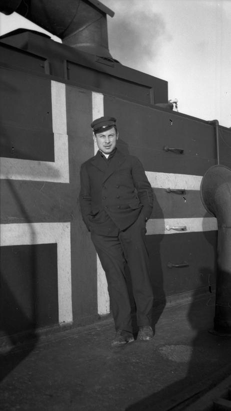 Styrmann Ferdinand Waage på dekk foran nøytralitetsflagg.