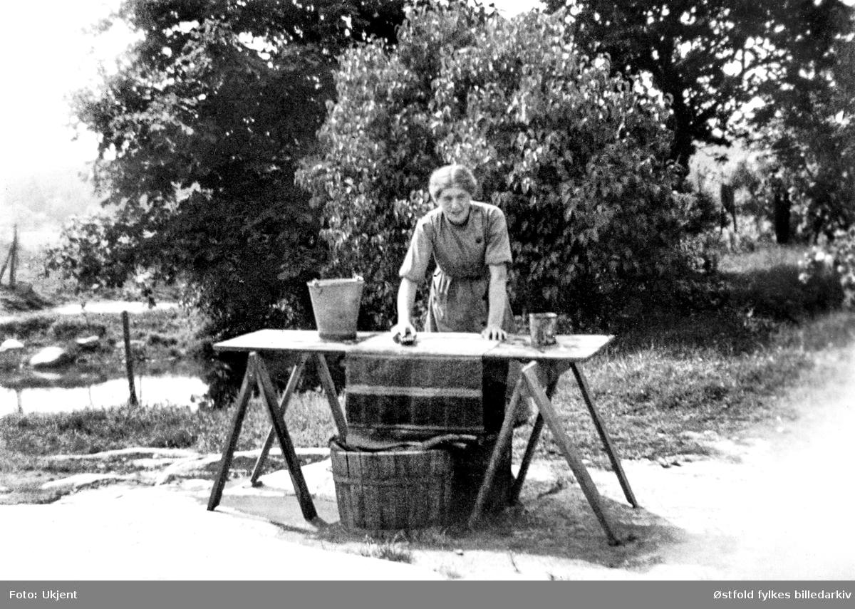 Adele Ringstad, f. Rostad (her ugift), skurer filleryer ved gårdsbrønnen på gården Rostad i Rolvsøy ca. 1935.